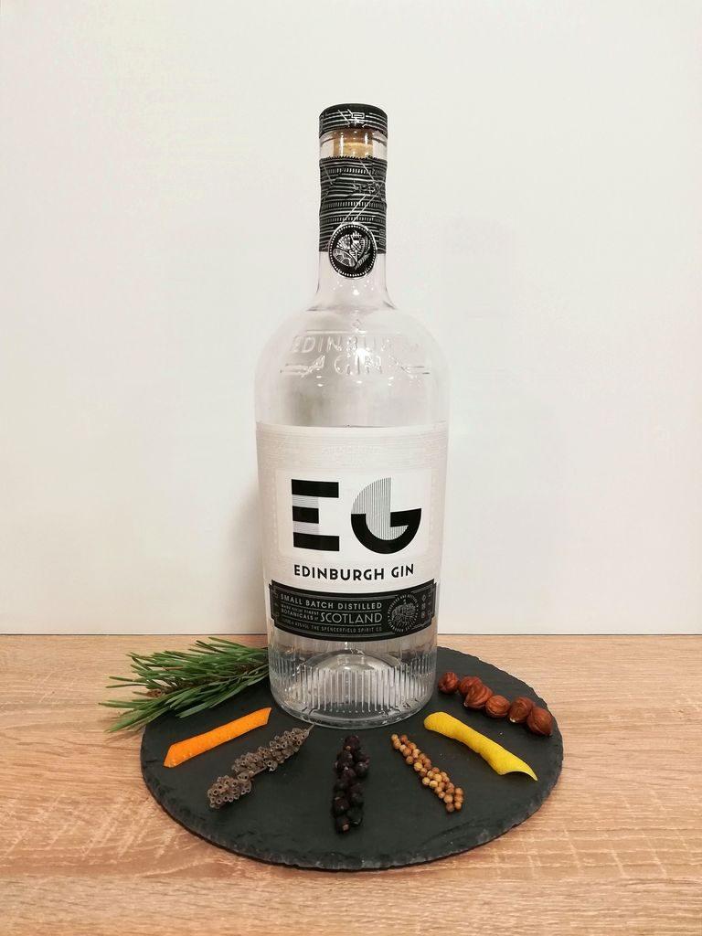 Edinburgh Gin Flasche mit verschiedenen Botanicals zur Dekoration