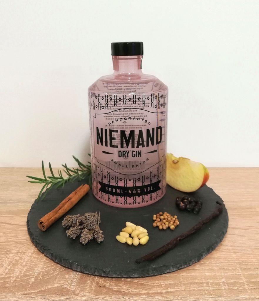 Niemand Dry Gin Flasche mit verschiedenen Botanicals zur Deko