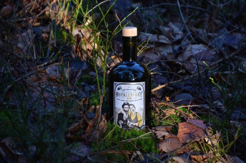 Eine Flasche Huckleberry Gin bei Sonnenaufgang auf einem Feld