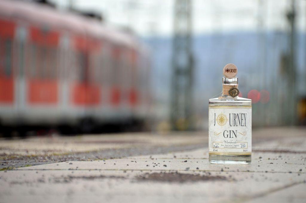 Journey Gin Flasche am Bahnhof mit einem Zug im Hintergrund