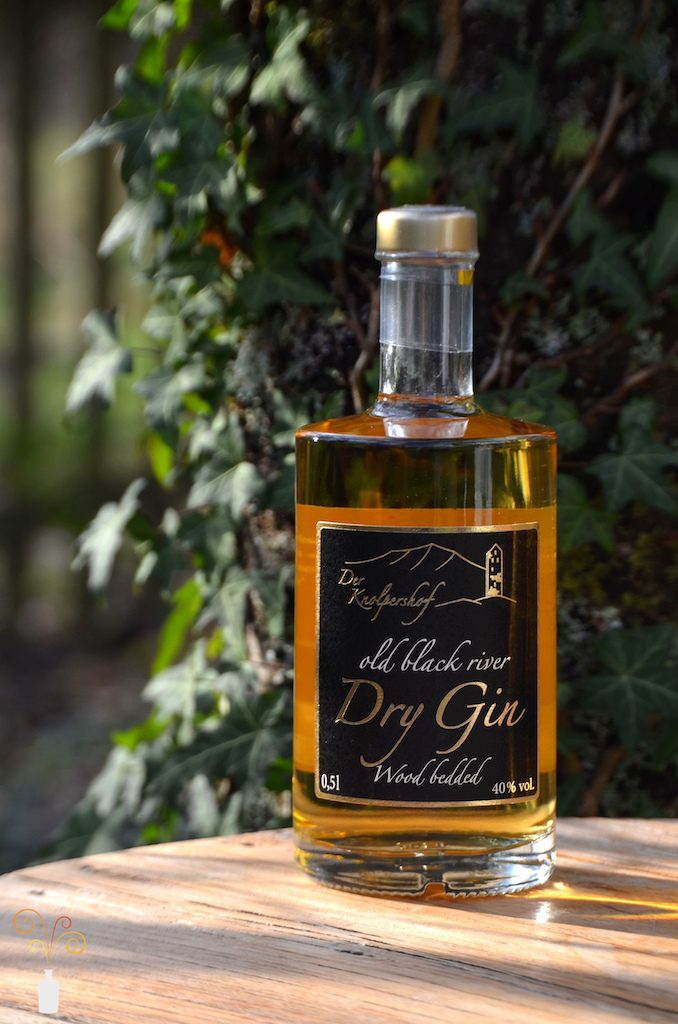 Eine Flasche Old Black River Dry Gin Wood Bedded