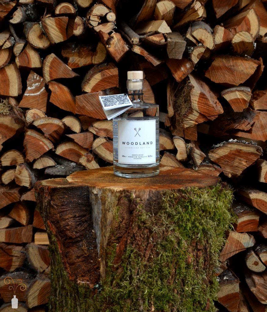 Eine Flasche des Woodland Sauerland Dry Gin vor einem Holzverschlag