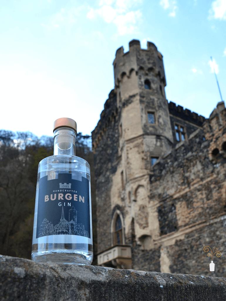 Eine Flasche des Burgen Gin vor einer Burg