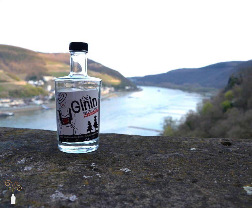 Eine Flasche Die Ginin alkoholfreier Gin vor einer Brücke