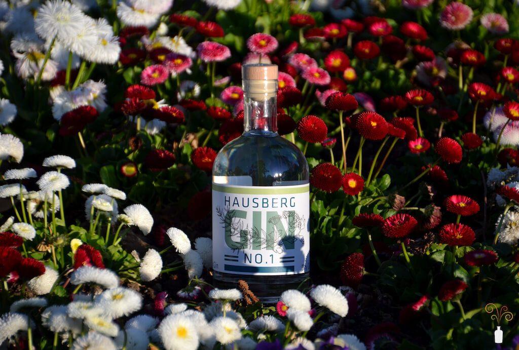 Eine Flasche des Hausberg No.1 Gin in einem Feld voller Blumen