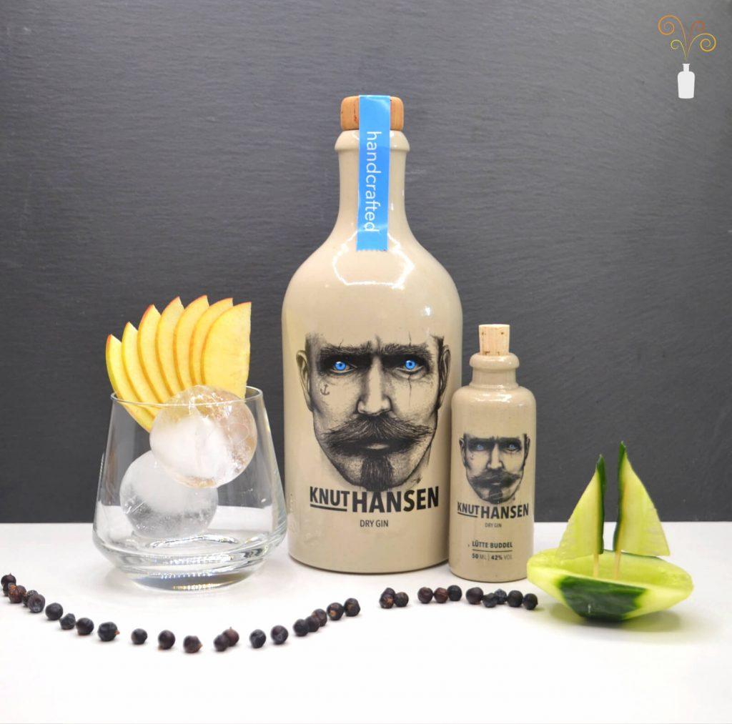 Eine große und kleine Flasche Knut Hansen Gin mit Dekoration und einem Gin-Glas
