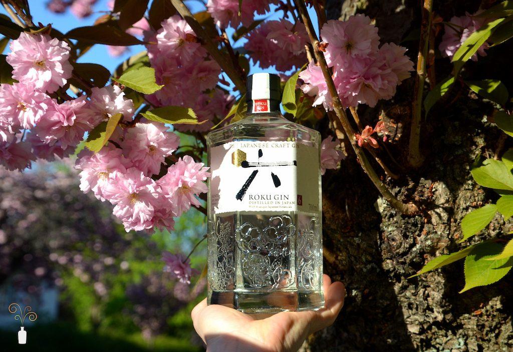 Eine Flasche Roku Gin vor einem blühenden Kirschbaum