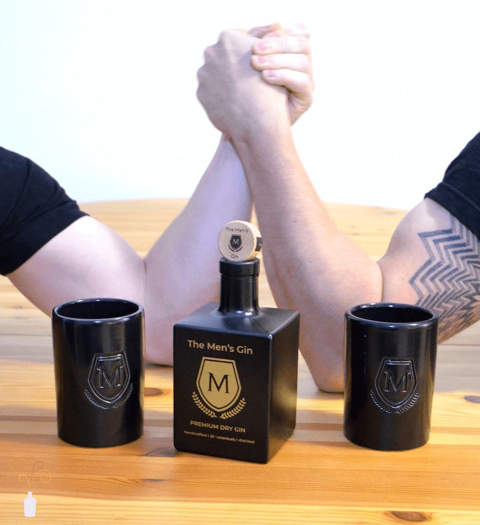 The Men's Gin Flasche mit zwei armdrückenden Männern im Hintergrund