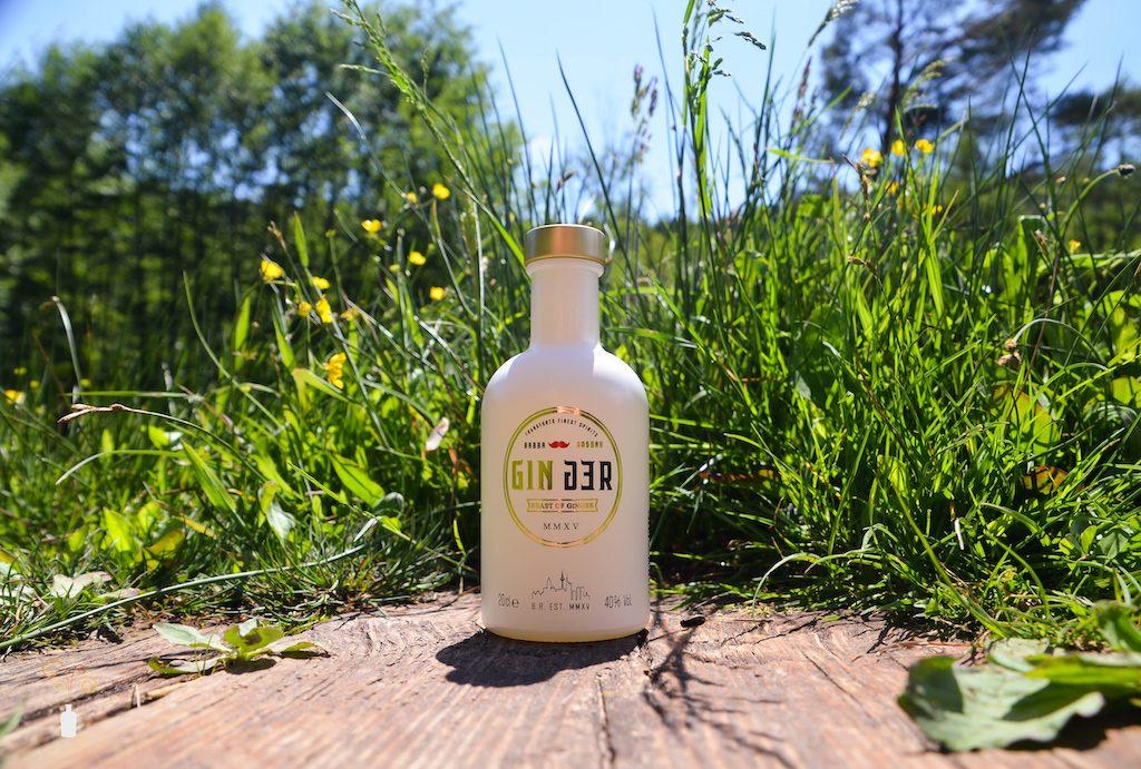 Eine Flasche Babba Rossas GINger Gin vor einem Feld voller Blumen