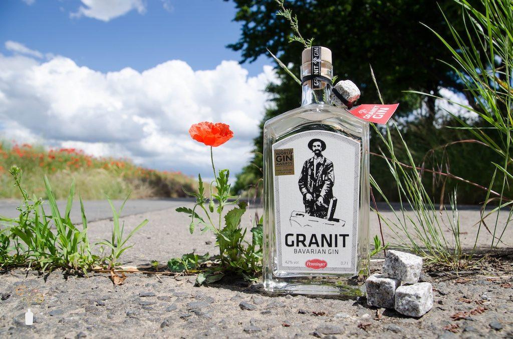 Penninger Granit Gin vor natürlichem Hintergrund mit einigen Granit-Würfeln