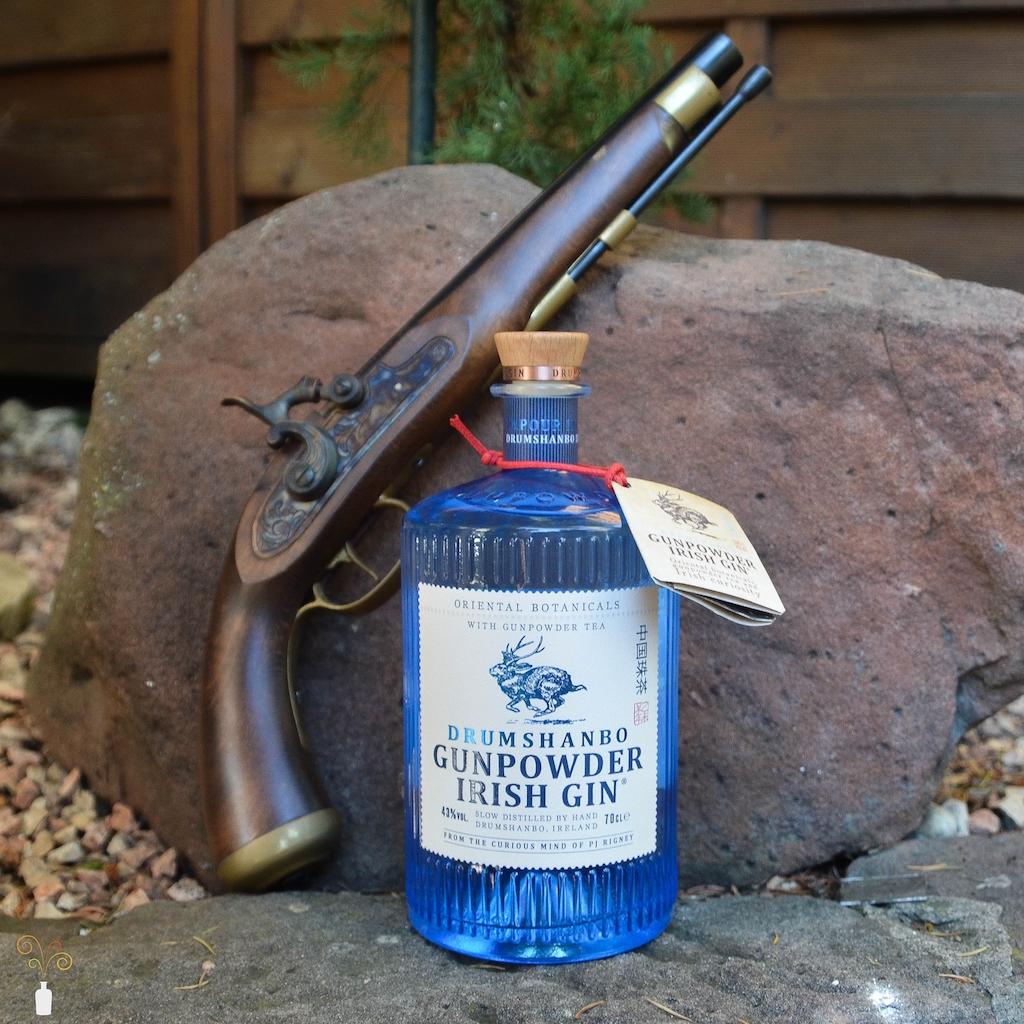 Eine Flasche des Drumshanbo Gunpowder Irish Gin mit alter Pistole zur Dekoration