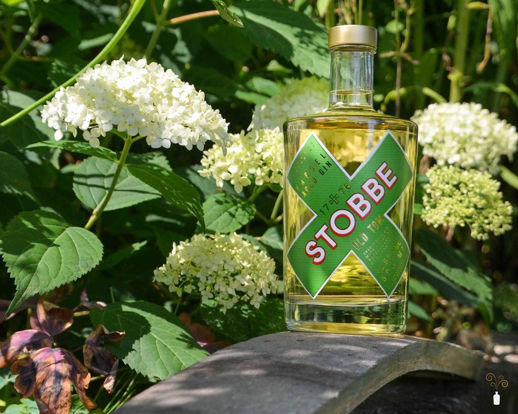 Vollansicht einer Flasche Stobbe 1776 Old Tom Gin vor Blumen im Garten
